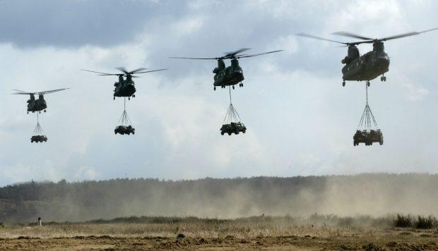 Polen, Zagan, 09 april 2003. ©Peter Wiezoreck Foto: Vier Cougar helikopters met LSV voertuigen eronder. (bron: defensie.nl)
